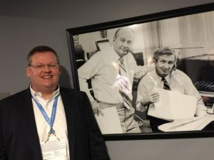 John Winborn, CIO for the Dallas Cowboys, poses next to a picture of two other innovators, Tex Schramm and Gil Brandt