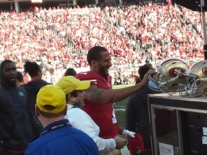 Colin Kaepernick exchanges his radio helmet for his flat-brimmed hat after throwing a TD pass