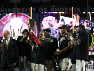 Alabama coach Nick Saban hoists the college championship trophy. Photo by Kent Gidley / University of Alabama