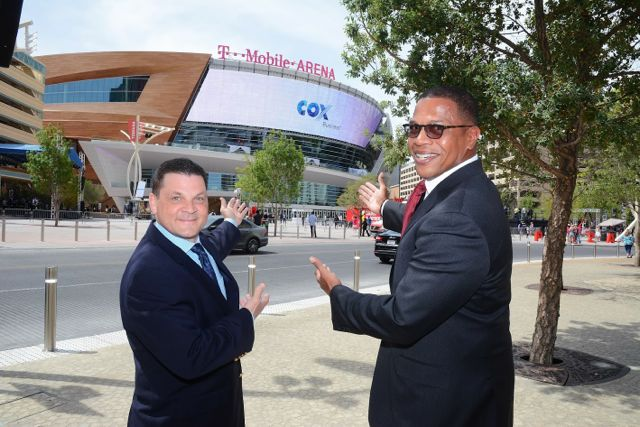 Jeff Breaux, vice president of western operations, Cox Business, (left) and Derrick R. Hill, vice president, Cox Business/Hospitality Network, gesture toward the exterior digital signage at T-Mobile Arena.